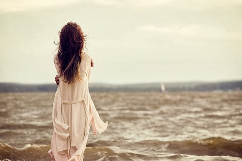 woman standing near the ocean with her back to us, pondering
