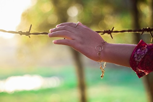 woman's hand  with bracelet and red shirt sleeve touching barbed wire- a symbol for not crossing boundaries