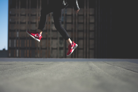woman with red tennis shoes jumping above concrete street
