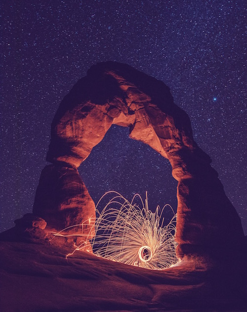 a circle of light flying outwards underneath a rainbow-shaped rock formation signifying change to shine your light