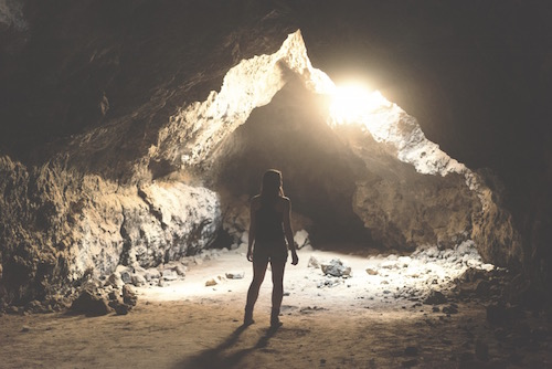 a woman standing at the entrance to a cave as a symbol for deepening intimacy