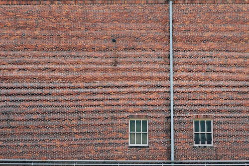 large brick wall with two windows in the bottom right corner as a symbol of building a marriage over the long run
