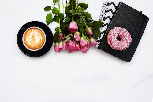 white background with symbols of self care arranged across the picture: roses, coffee, a journal, a donut