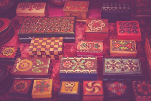 colorful carved boxes on a red table as symbols of tools to use to undo stress