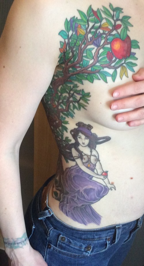 Tree branches and a semi-naked woman tattooed across a Caucasian woman's chest and ribcage