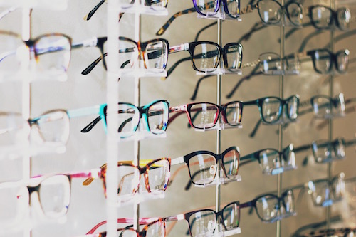 a wall of eye glasses frames as a symbol of seeing things differently at mid-life