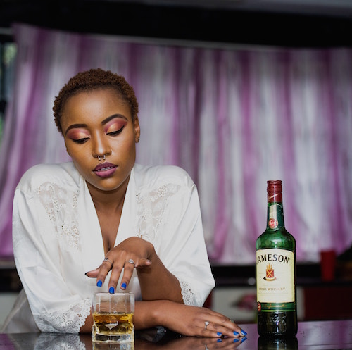 a dark-skinned woman wearing a white silky robe running her fingers around the rim of a glass with Jameson whiskey in it