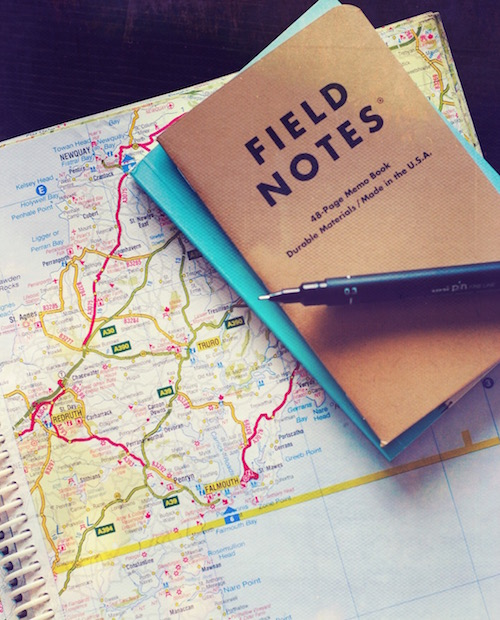 A map with a notebook and a pen atop it as a symbol of guiding ourselves through the holidays