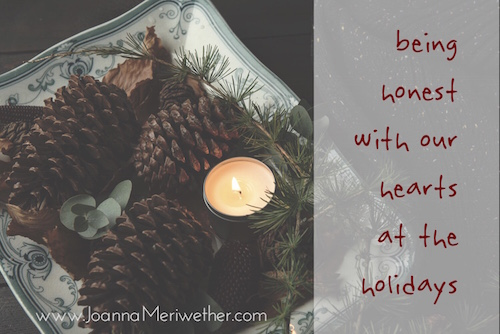 "a small candle next to some pine cones and pine boughs with the words ""being honest with our hearts at the holidays"" on the left side"