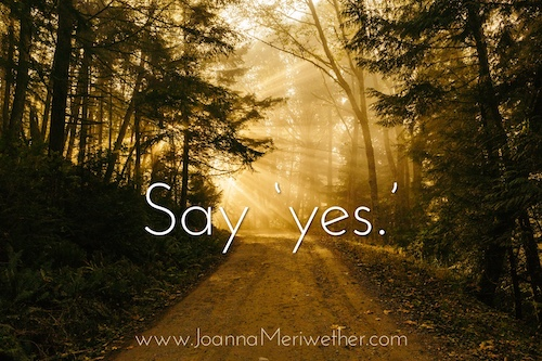 a road that is partly in darkness heading towards sunlight with the words 'say yes' across the pathway